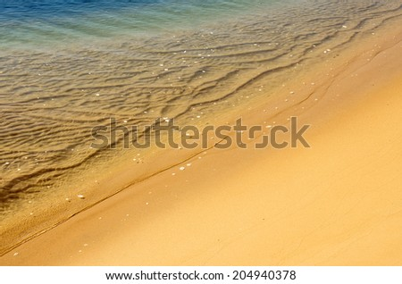 Serene sea shore closeup with calm water over sand - stock photo