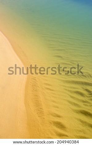 Serene sea shore closeup with calm water over sand - stock photo