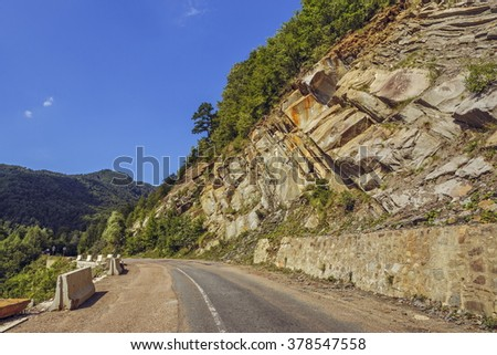 Serene summer landscape with steep rocky cliff alongside a road crossing the Siriu mountains in Buzau county, Romania. - stock photo