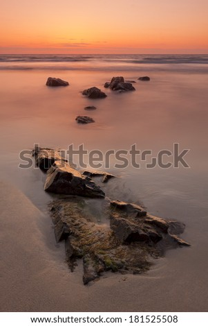 Serene Sunset at Sennen Cove - Rocky shoreline and flat water with an orange sunset sky - stock photo