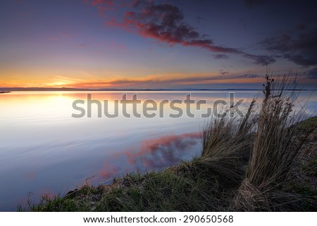 Serene sunset by the banks of Tuggerah Lake on the Central Coast of NSW - stock photo
