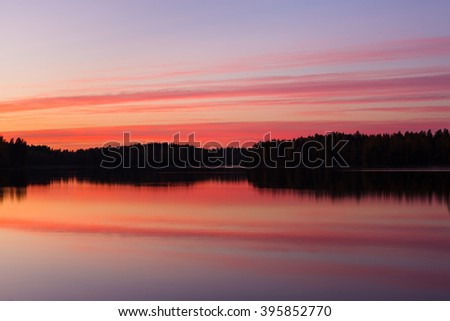Serene view of calm lake and tree silhouettes - stock photo
