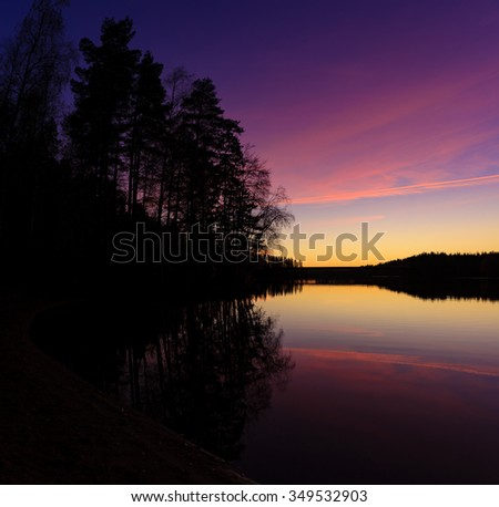 Serene view of calm lake and tree silhouettes at twilight