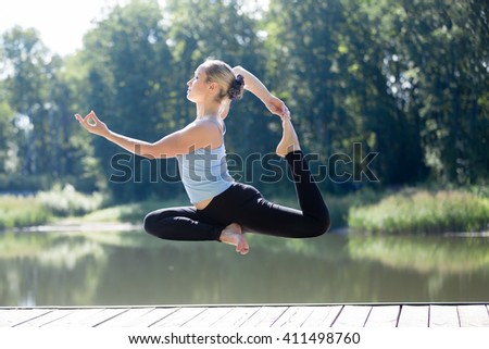 Serene young sporty beautiful woman floating in midair during yoga practice, levitating above ground in Eka Pada Rajakapotasana (One Legged King Pigeon Posture), working out outdoors in summer - stock photo