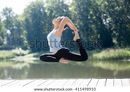 Serene young sporty beautiful woman floating in midair during yoga practice, levitating above ground in EkaPada Radjakapotasana (One-Legged King Pigeon Posture), working out outdoors in park - stock photo