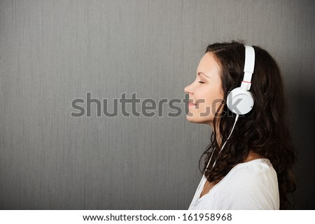 Serene young woman enjoying her music standing in profile listening to her headphones with a smile of pleasure, on a grey background with copyspace - stock photo