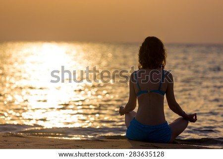 Serene young woman practicing yoga, Sitting in Easy (Decent, Pleasant Pose), Sukhasana, meditating, relaxing on the sea coast at sunset or sunrise, copy space, back view - stock photo