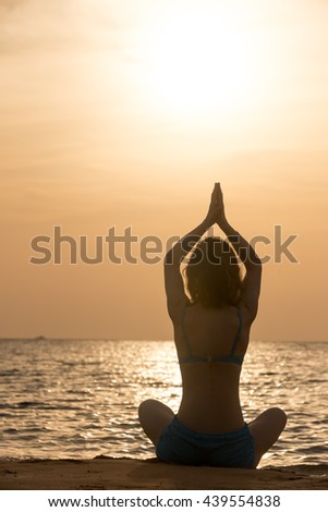 Serene young woman practicing yoga, Sitting on the sea coast at sunset or sunrise in Easy (Pleasant Pose), Sukhasana, hands above head, back view, vertical shot - stock photo