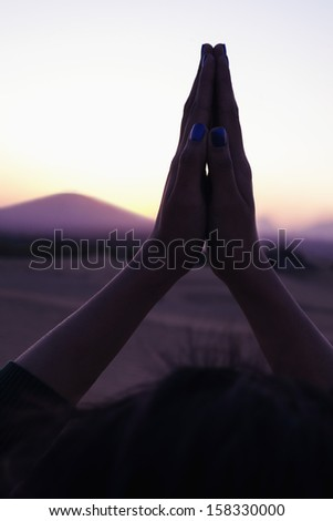 Serene young woman praying with her palms together  - stock photo