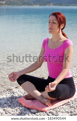 Serene young woman sitting barefoot in casual clothes in the lotus position meditating alongside a lake while enjoying a healthy outdoor lifestyle in Provence, France. - stock photo