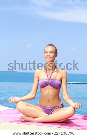 Serene young woman with a smile of pleasure sitting meditating in the lotus position in her bikini at the edge of an infinity pool overlooking the ocean - stock photo