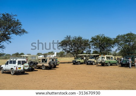 SERENGETI, TANZANIA - AUGUST 27, 2015: Safari cars waiting to clients in the Kogatende airstrip in northern Serengeti, Tanzania, Africa - stock photo