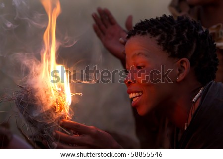 SERENGETI, TANZANIA - JUNE 6: Unidentified Bushman women making fire on June 6, 2010 in the Serengeti, Tanzania. - stock photo