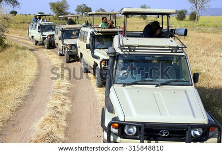 SERENGETI - TANZANIA ; Photographers and tourists are spotting wildlife during a safari on a 4x4 Jeep through a National Park in Africa on june 12, 2013 - stock photo