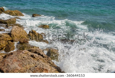 Serenity beach with waves hitting rocks
