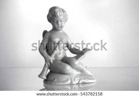 serial porcelain figurine of an angel playing a flute from the decor store - The Decor Store