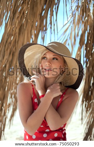 Series closeup portrait of beautiful female model in a hat under a palm tree - stock photo