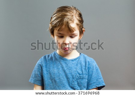 Series of a Little Boy, Expressions - the Rascal got caught, and is looking down, ashamed - stock photo
