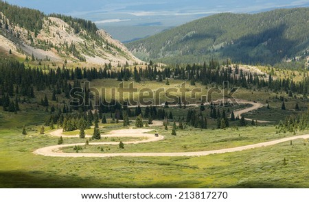 Series of bends on unfinished or dirt road climbing to top of Cottonwood Pass in Colorado - stock photo
