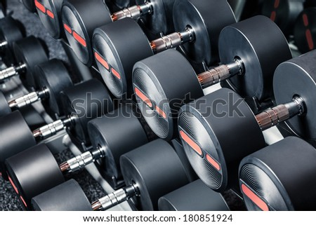 Series of dumbbells are on stand at the gym - stock photo