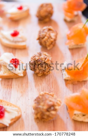 Series of Hors D'oeuvres on a wooden platter - stock photo