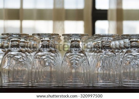 Series of inverted empty wine glasses arranged in several rows. - stock photo
