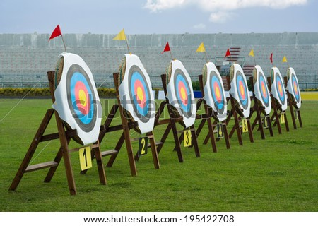 Series of straw archery targets in wooden stands inside football stadium - stock photo