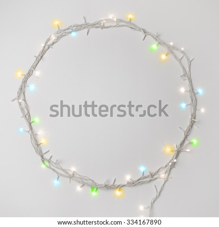 Series of tiny christmas lights. Round shape border made with decorative lights. - stock photo