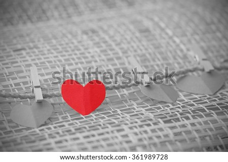 Series of Valentines Card. Four Red heart paper cut with clothes pin on wooden weaving background, in very shallow focus. Image of Valentines day. Selective Color. - stock photo