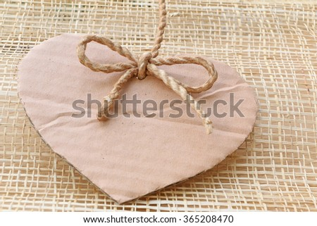 Series of Valentines Card, Heart Shape Blank Cardboard with Flax Cord hanging on wooden weaving  background. - stock photo