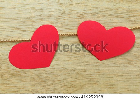 Series of Valentines Card. Red heart paper cut with clothes pin on wooden background, in very shallow focus. Image of Valentines day. - stock photo