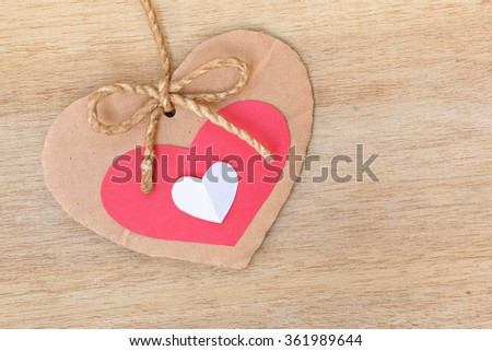 Series of Valentines Card, Three Heart Shape Blank Cardboard with Flax Cord hanging over wood background. - stock photo