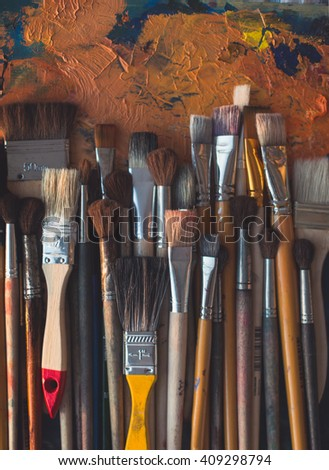 Series of wooden different size paintbrushes lying on palette with old oil paint cracked texture in art studio, top view image. - stock photo