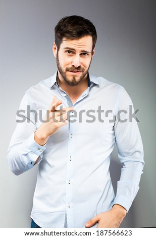 serios man in blue shirt on grey background