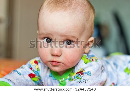 Serious adorable newborn baby boy portrait looking at camera - stock photo