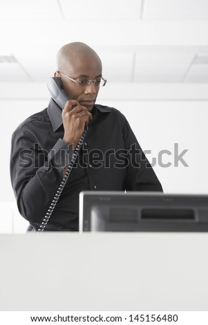 Serious African American businessman using telephone at computer desk - stock photo
