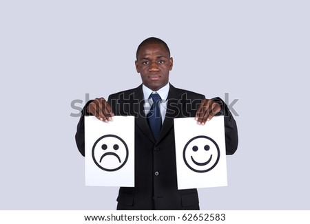 serious african businessman holding face symbols printed on a paper - stock photo
