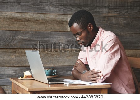 Serious African businessman using laptop while sitting at a coffee shop, looking at the screen with serious concentrated expression, thinking of a problem, resting his folded arms on the table - stock photo