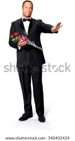 Serious African man with short black hair in evening outfit holding flowers - Isolated