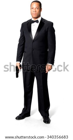 Serious African man with short black hair in evening outfit holding handgun - Isolated