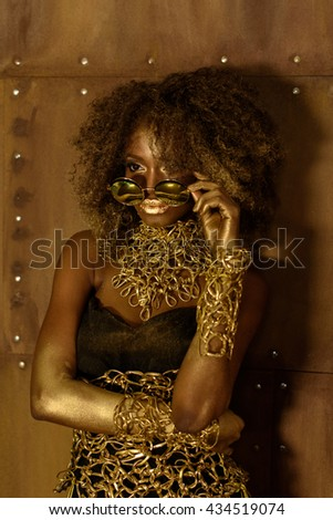 Serious African young woman with an afro hairstyle wearing sunglasses and gold fashion stylization