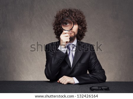 serious afro style haired young businessman looking through a magnifying glass on grunge background - stock photo