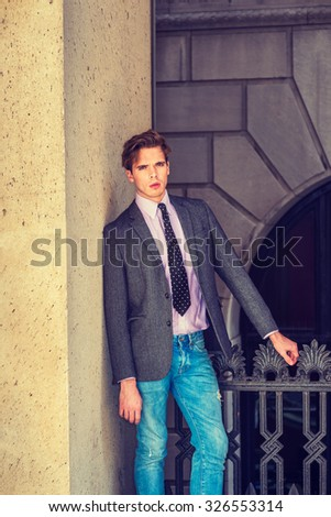 Serious American businessman in New York. Wearing blazer, necktie, jeans, a young college student standing by railing on balcony outside office, thinking, lost in thought. Instagram filtered effect.  - stock photo