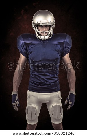Serious American football player standing against dark background