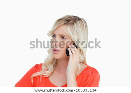 Serious and attractive young woman talking on the phone while looking on the side - stock photo