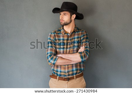Serious and confident cowboy. Handsome young man in cowboy hat keeping arms crossed and looking away while standing against grey background  - stock photo