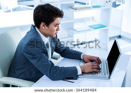 Serious asian businessman using his computer in his office - stock photo