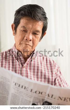 Serious Asian man reading newspaper - stock photo