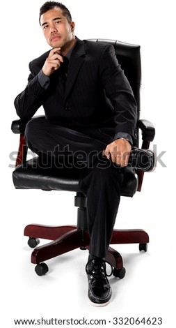 Serious Asian man with short black hair in business formal outfit with hands holding leg - Isolated