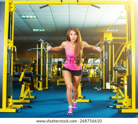 serious athletic woman pumping up muscles in a gym - stock photo